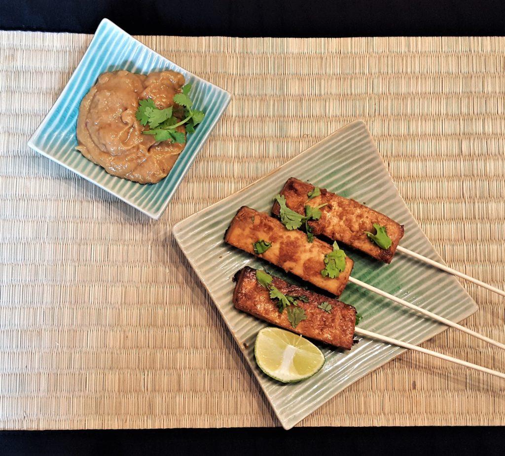 Tofu-Satay Spieße auf grünem Teller mit Zitronenstück und Koriander, daneben türkiser Teller mit Erdnuss-Dp und Koriander, alles auf Bastmatte