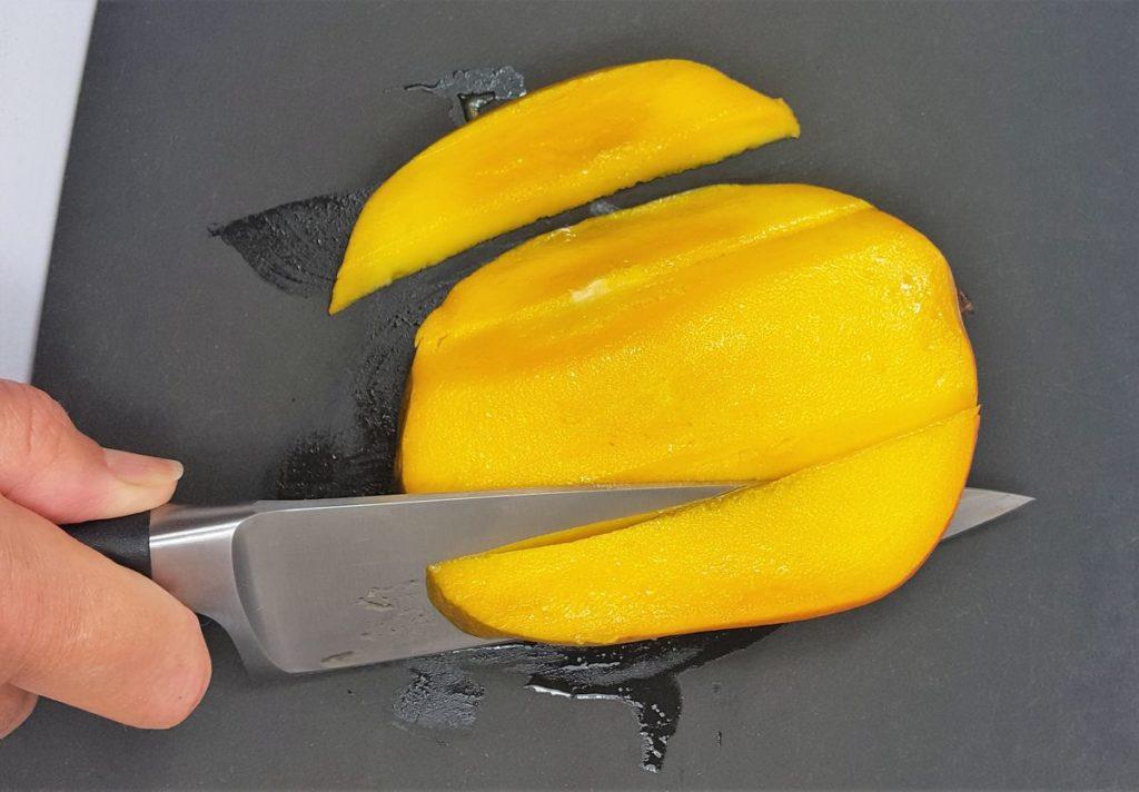 Mangofleisch wird mit einem Messer schräg vom Kern geschnitten