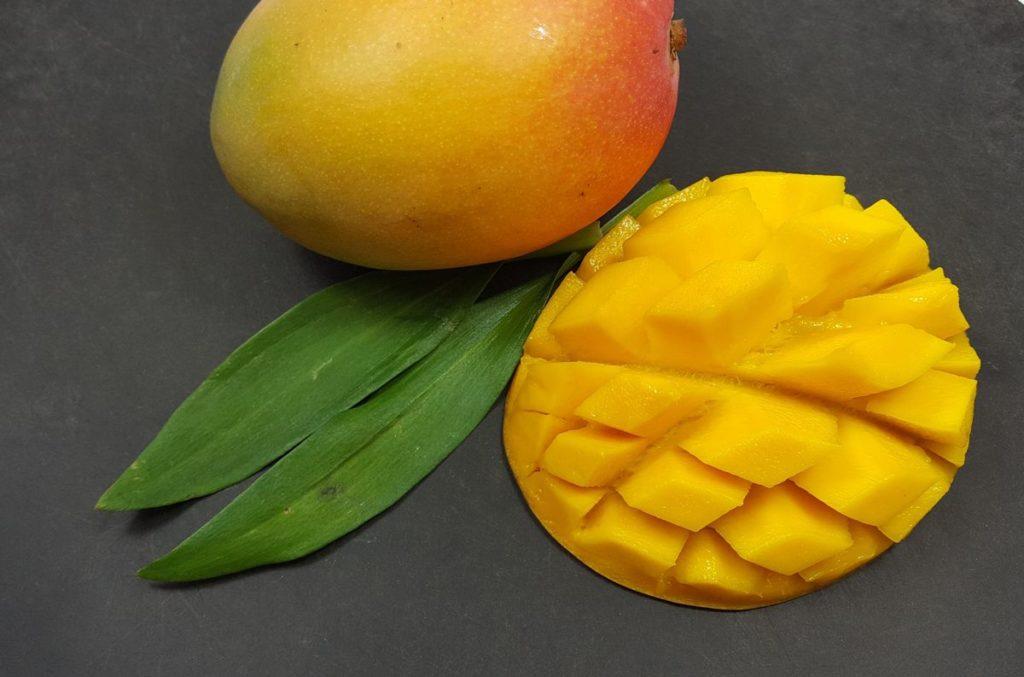 ganze Mango und Mango-Igel auf schwarzem Untergrund