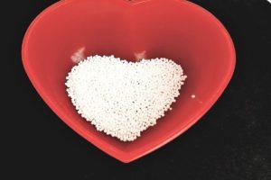 Tapioka-Kügelchen in roter Herzschale auf schwarzem Untergrund