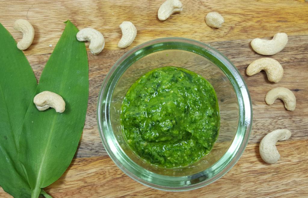 Bärlauch-Pesto im Glas auf Holzbrett mit Cashewkernen und Bärlauchblättern von oben fotografiert