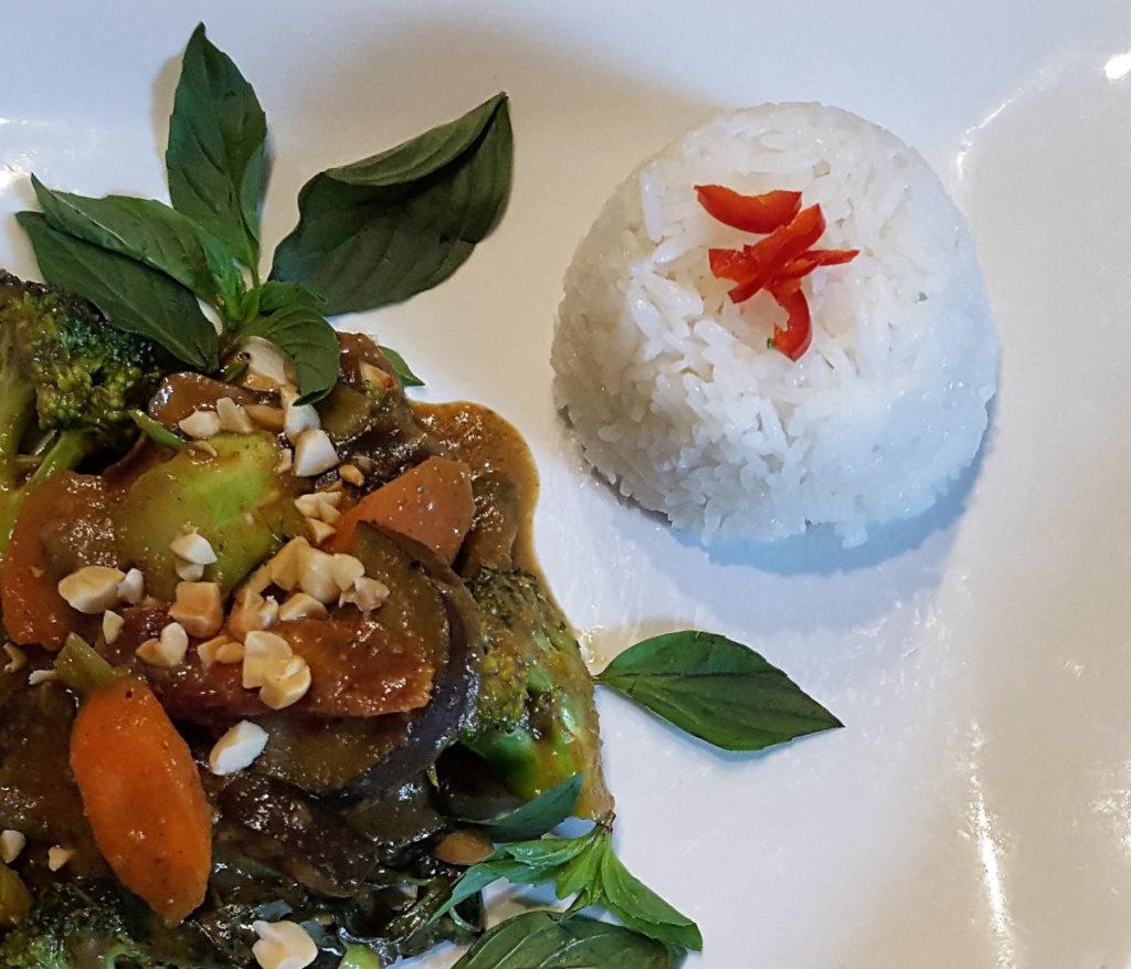 gekochter Reis mit Curry auf einem weißen Teller