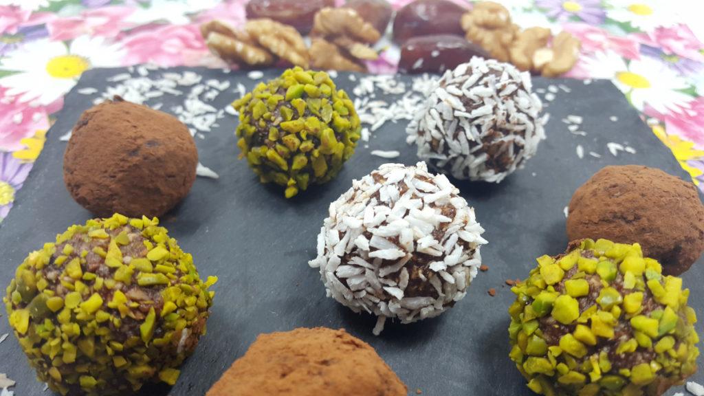 Bliss Balls Energy Balls aus Datteln mit Kokosraspeln, Pistazienkernen, Kakaopulver ummantelt. Auf einem schwarzen Brett auf Blumenuntergrund.