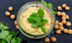 Hummus im Glas mit Koriander auf schwarzem Untergrund