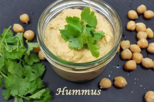 Hummus im Glas auf schwarzem Untergrund mit Kichererbsen und Koriander