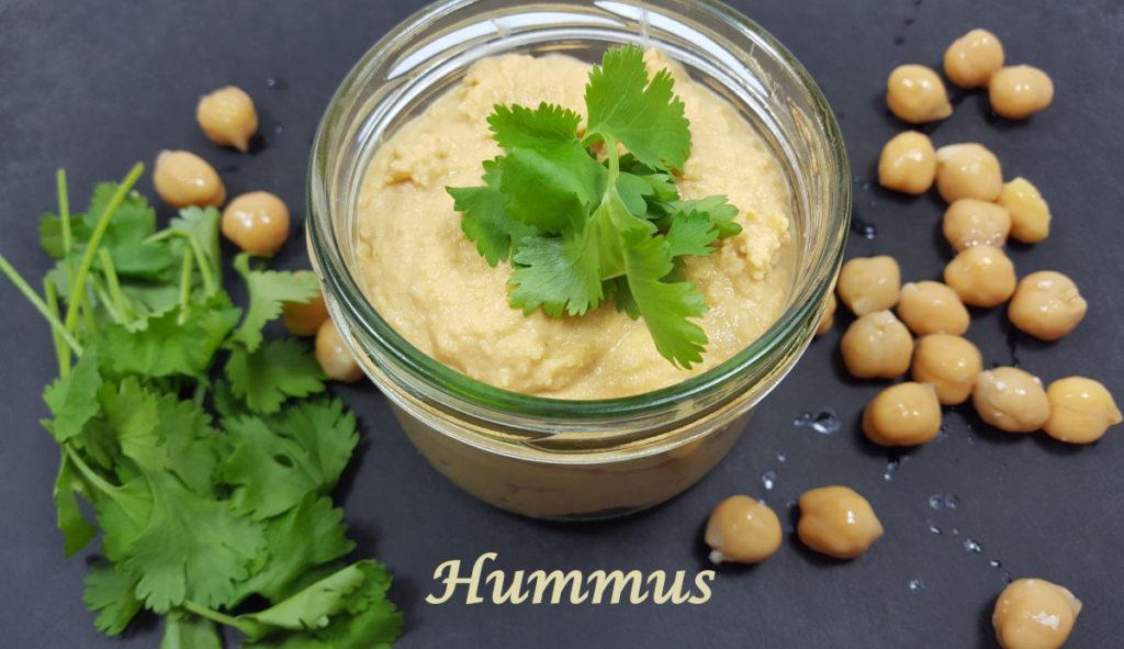Hummus im Glas auf schwarzem Grund mit Kichererbsen und Koriander