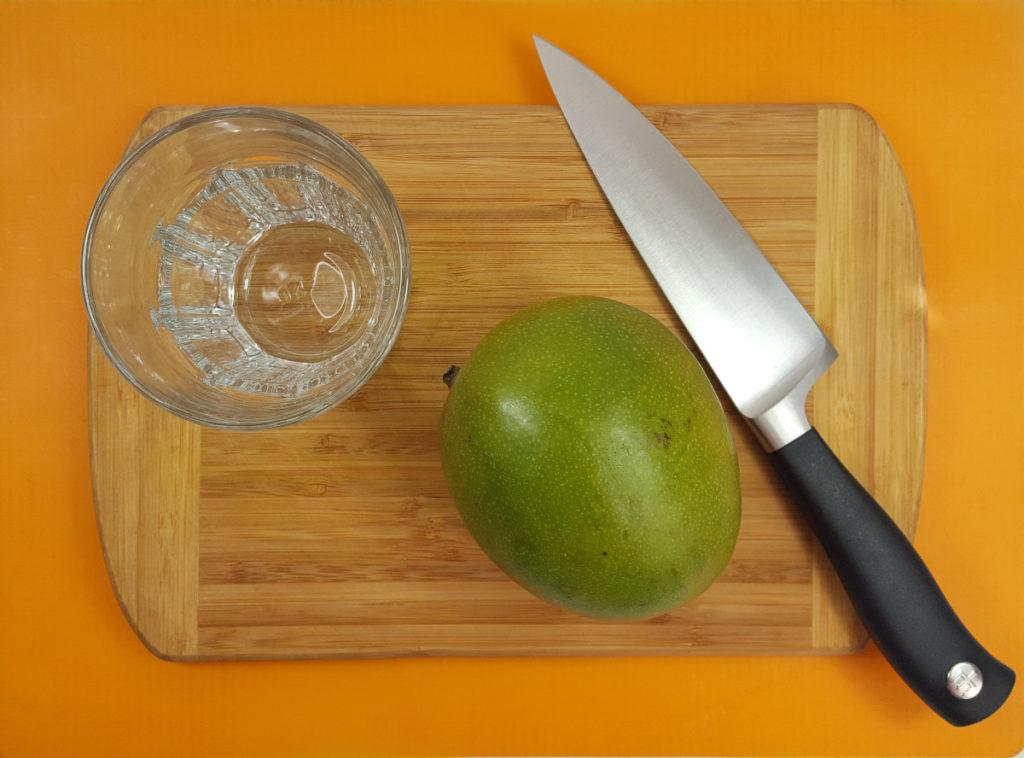 Mango schälen: Ganze Mango, Glas und Messer auf einem Brett auf orangenem Untergrund.