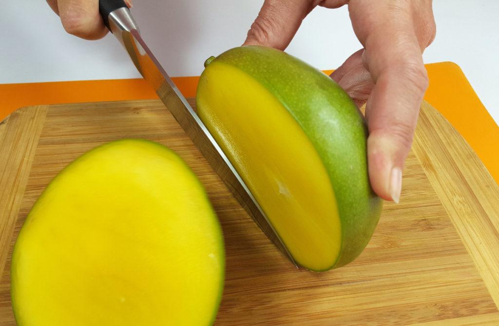 Mango schälen: EIne Backe der Mango wird mit einem Messer abgeschnitten. Auf Brett.