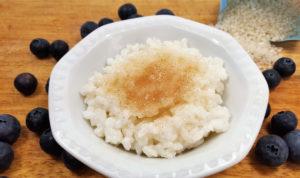 Milchreis mit Zimt und Zucker in weißem Schälchen mit Heidelbeeren