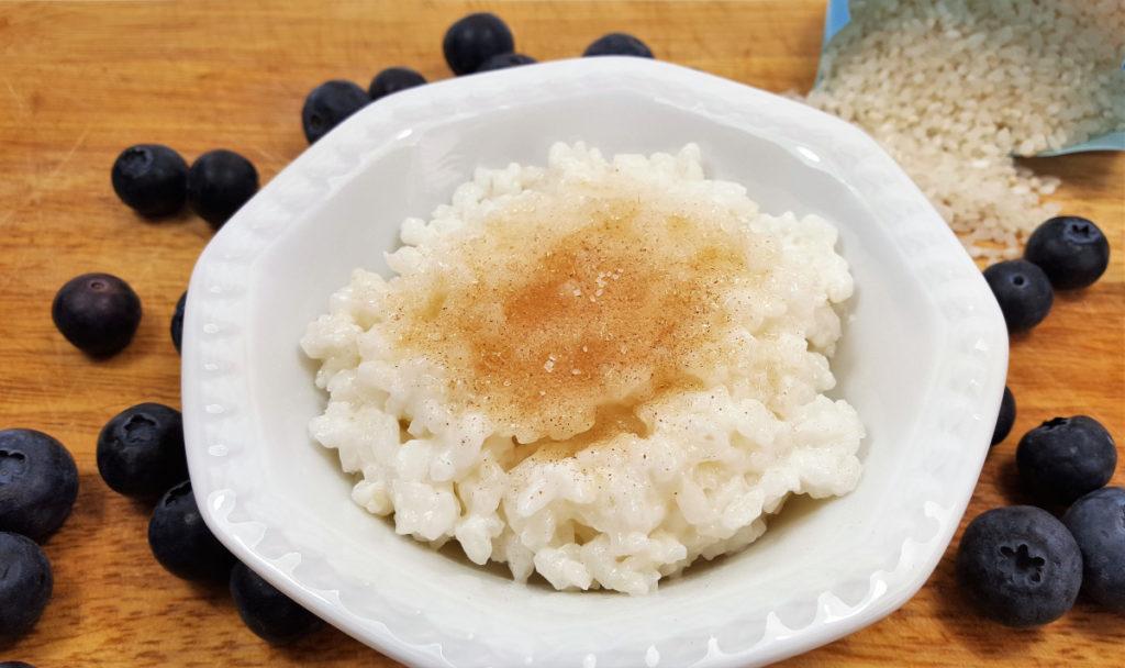 Milchreis mit Zimt und Zucker in weißem Schälchen auf Holzbrett mit Heidelbeeren