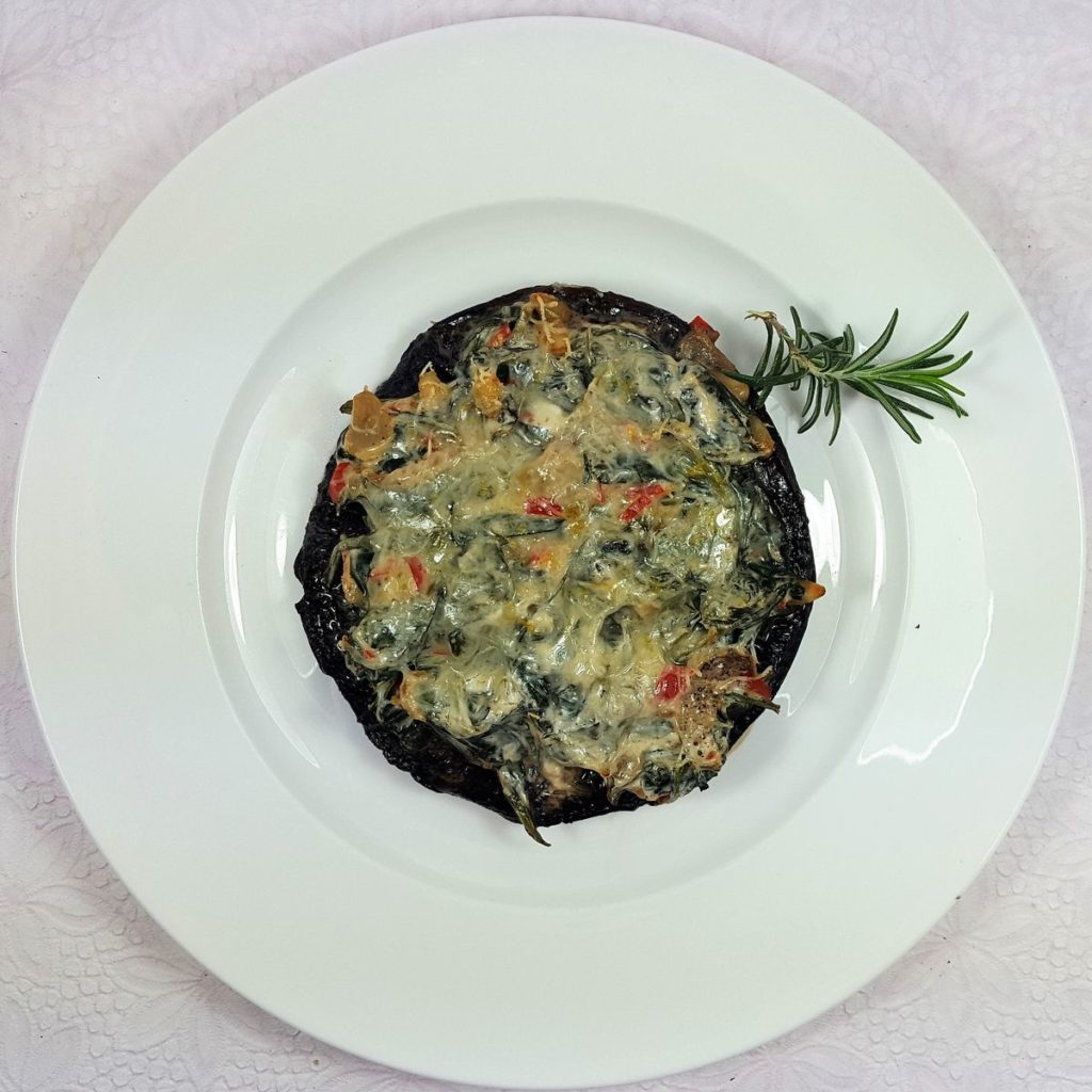 gefüllter, überbackener Portobello mit Rosmarin auf weißem Teller