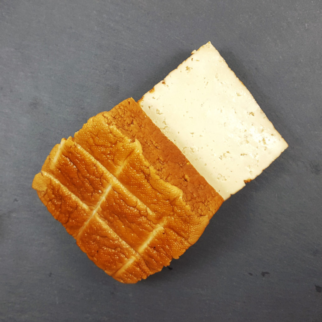 geräucherter Tofu, aufgeschnitten, auf schwarzem Untergrund