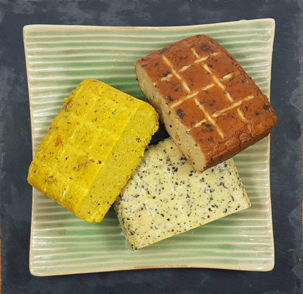 Curry-Tofu, Räucher-Tofu, Tofu mit Kräutern auf grüner quadratischer Schale und schwarzem Hintergund