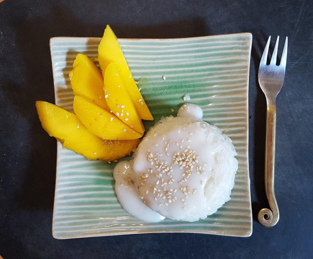 Sticky Rice mit Mango, Kokoslmilch, Sesam auf grünem Teller mit Gabel auf schwarzem Untergrund