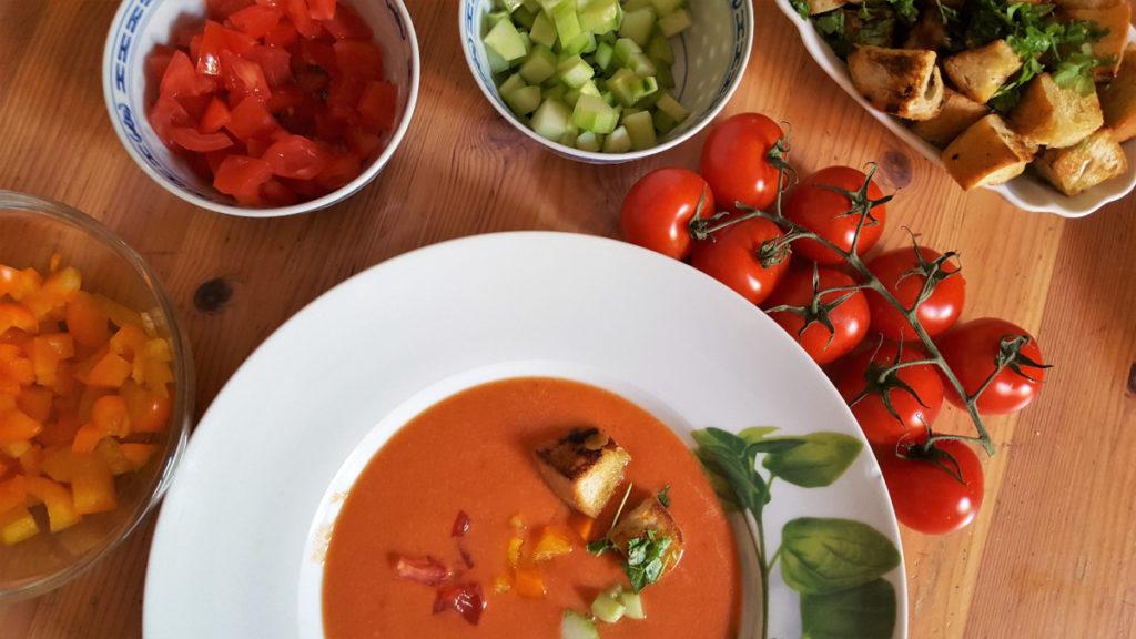 Gazpacho kalte Gemüsesuppe in weißem Suppenteller mit Strauchtomaten, Gemüseschälchen auf Holztisch