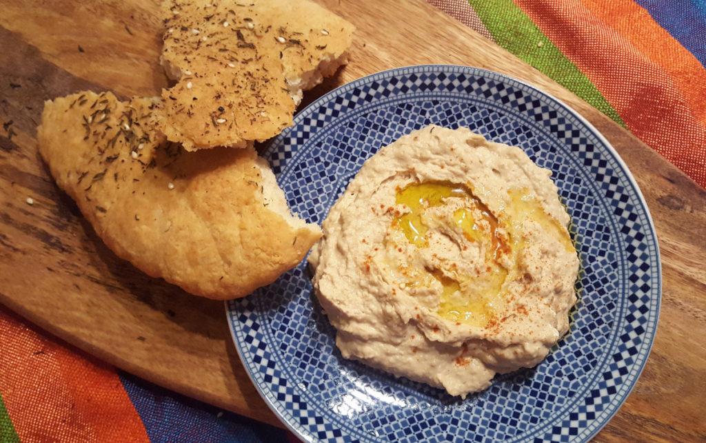 Hummus auf blau-weißem Teller mit Fladenbrot auf Brett auf but gestreiftem Tuch