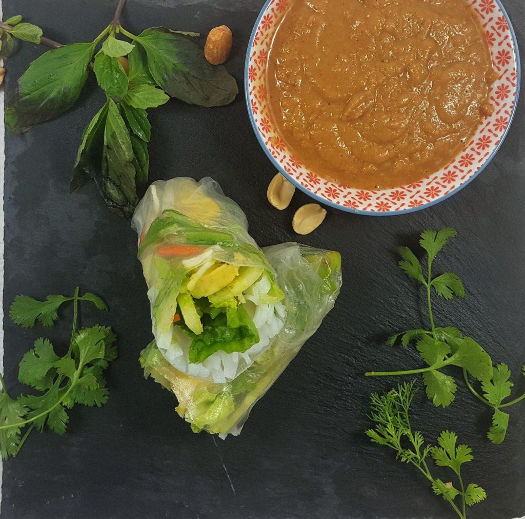 Sommerrolle aufgeschnitten mit Erdnussdip, Koriander, Thaibasilikum, Erdnüssen auf schwarzem Untergrund