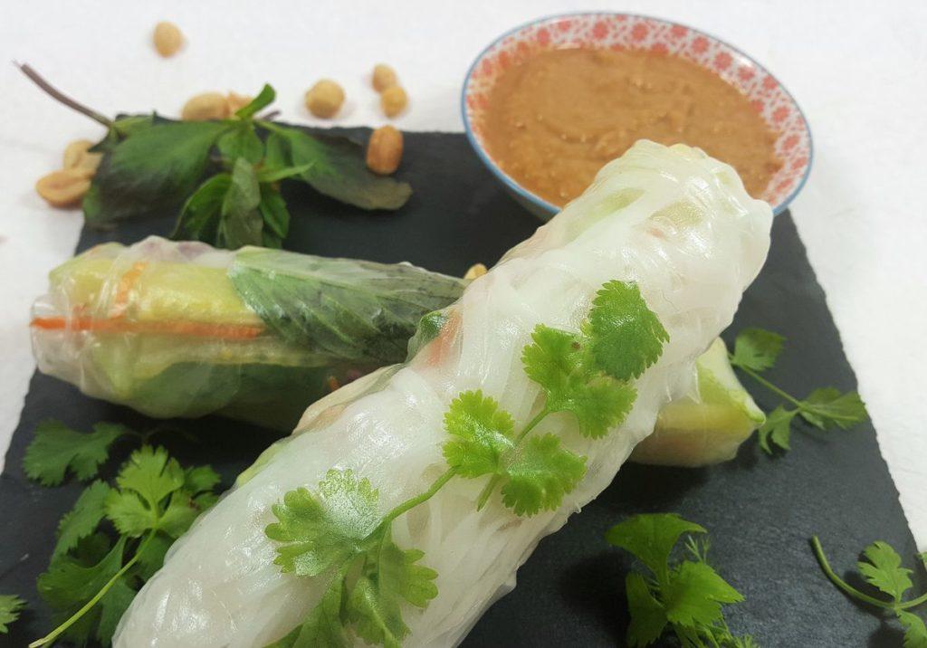 2 Sommerrollen mit Koriander, Thai-Basilikum, Erdnüssen und Erdnussdip auf Schieferbrett