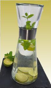 Karaffe mit Leitungswasser, Limettenscheiben, Pfefferminze auf schwarzem Brett vor gelbem Hintergrund