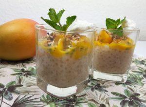 2 Gläser mit Tapioka-Kokos-Pudding, Mango und Passionsfrucht und Minzezweig und eine Mango
