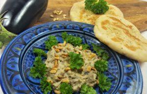 Baba Ganoush und Fladenbrot auf einem blauen Teller, mit Aubergine, Petersilie, Pinienkernen