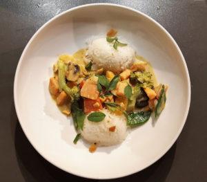 Gelbes Curry mit Reis auf weißem Teller beim Kochkurs im Kochhaus