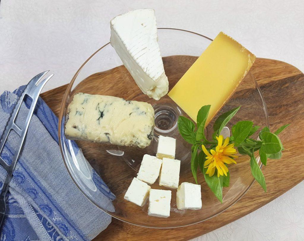 Käse vegetarisch: Gorgonzola, Camembert, Appenzeller, Schafskäse auf Glasplatte auf Brett