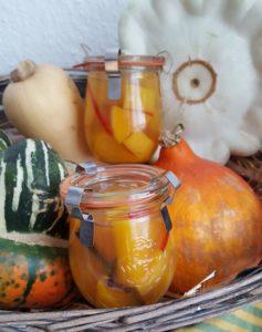 süß-saure Kürbis-Pickles in Gläsern zwischen Kürbissen im Korb
