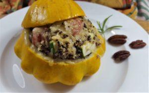 Patisson gefüllt mit Quinoa auf weißem Teller mit Pekannüssen und Rosmarin