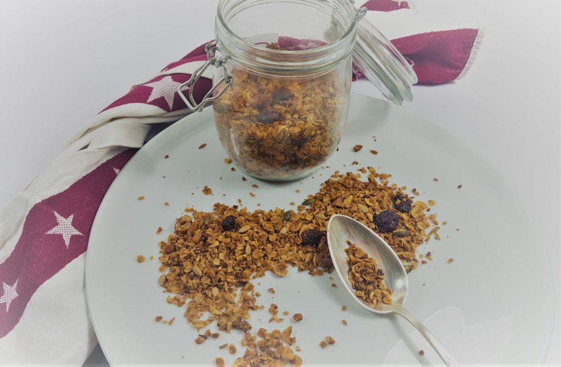 Granola auf weißem Teller mit Löffel