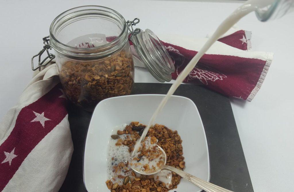 Granola in Schälchen mit Löffel und Milch